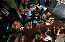 FILE - In this May 30, 2019 file photo, Honduran migrant children eat a meal at the Jesus el Buen Pastor del Pobre y el Migrante shelter in Tapachula, Chiapas state, Mexico. The federal government will be opening a facility at an Army base in…