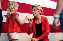 Democratic presidential candidate Sen. Elizabeth Warren, D-Mass., right, makes a pinky promise as she chats with Sydney Hansen, 8, of Oakland, Calif., during a campaign stop at town hall in Peterborough, N.H., Monday, July 8, 2019. (AP Photo/Charles…