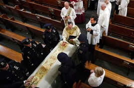 Rev. John P. Harrington blesses the casket during the funeral ceremony for Detective Luis Alvarez, at Immaculate Conception Church, in the Queens borough of New York, Wednesday, July 3, 2019. Alvarez, 53, who died after a three-year battle with…