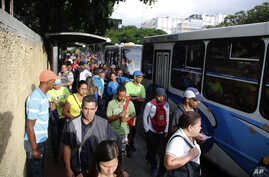 People stand in a bus line in Caracas, Venezuela, Tuesday, July 23, 2019. The lights were returning to life early Tuesday across Venezuela following a massive blackout a day earlier that crippled communications, froze the Caracas metro and snarled…