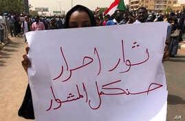 """A Sudanese protester holds an Arabic placard that reads: """"Free revolutionaries will continue the path,"""" during a demonstration against the military council, in Khartoum, Sudan, Sunday, June 30, 2019. Tens of thousands of protesters have taken to the…"""