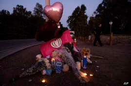 Paramedic Rebecca Mackowiak passes a makeshift memorial for Gilroy Garlic Festival shooting victims outside the festival grounds, Monday, July 29, 2019, in Gilroy, Calif. (AP Photo/Noah Berger)