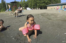 Milana Acuna, 5, makes a mud creation while at Goose Lake as her father, Manny Acuna, looks on, July 5, 2019, in Anchorage, Alaska.