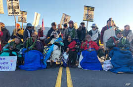 Demonstrators gather to block a road at the base of Hawaii's tallest mountain, Monday, July 15, 2019, in Mauna Kea, Hawaii, to protest the construction of a giant telescope on land that some Native Hawaiians consider sacred. (AP Photo/Caleb Jones)
