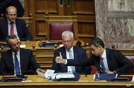 Greece's Prime Minister Kyriakos Mitsotakis, right, gives a thump up to Greek Finance Minister Christos Staikouras, left, as Deputy Prime Minister Panagiotis Pikrammenos, center, looks on during a parliamentary session in Athens, on Saturday, July…