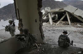 In this Tuesday, Nov. 3, 2009 photo, U.S. soldiers from the 2nd Battalion, 12th Infantry Regiment, 4th Brigade Combat Team, 4th Infantry Division wait inside a destroyed health clinic in the village of Qatar Kala in the Pech Valley of Afghanistan's Kunar province.