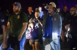 Police officers escort people from Christmas Hill Park following a deadly shooting during the Gilroy Garlic Festival, in Gilroy, Calif., on Sunday, July 28, 2019. (AP Photo/Noah Berger)