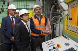 "Ukrainian President Volodymyr Zelenskiy, foreground, visits the ""new safe confinement"" shelter that spans the remains of the Chernobyl nuclear power plant's Reactor No. 4, in Chernobyl, Ukraine,  July 10, 2019."