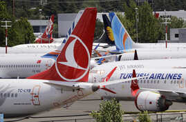 FILE - In this June 27, 2019, photo dozens of grounded Boeing 737 MAX airplanes crowd a parking area adjacent to Boeing Field in Seattle.