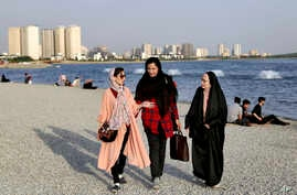 In this Saturday, July 6, 2019 photo, women walk on the shore of the Persian Gulf Martyrs' Lake in Tehran, Iran.  A few daring women in Iran's capital have been taking off their mandatory headscarves, or hijabs, in public, risking arrest and drawing…