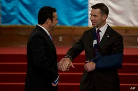 Acting Department of Homeland Security Secretary Kevin McAleenan, right, and Guatemalan President Jimmy Morales shake hands at the National Palace in Guatemala CIty, May 27, 2019.