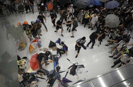 Policemen scuffle with protesters inside a shopping mall in Sha Tin District in Hong Kong, Sunday, July 14, 2019. Police in Hong Kong have fought with protesters as they broke up a demonstration by thousands of people demanding the resignation of…