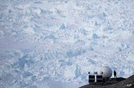 In this Aug. 16, 2019, photo, a woman stands next to an antenna at an NYU base camp at the Helheim glacier in Greenland. Summer 2019 is hitting the island hard with record-shattering heat and extreme melt.