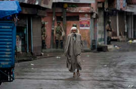 A Kashmiri man walks as Indian paramilitary soldiers stand guard during security lockdown in Srinagar, Indian controlled Kashmir, Wednesday, Aug. 14, 2019. India has maintained an unprecedented security lockdown to try to stave off a violent…