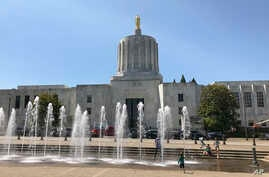 Children play in fountains at the Oregon State Capitol while inside the Senate meets after a boycott over a climate-change bill ended, in Salem, June 29, 2019.