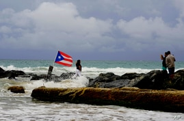 A woman poses for a photo backdropped by ocean waters and a Puerto Rican national flag, after the passing of Tropical Storm Dorian, in the Condado district of San Juan, Puerto Rico, Wednesday, Aug. 28, 2019. The Hurricane Center said the storm could…
