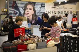 Shoppers browse goods for sale at a discount retailer in a shopping mall in Beijing, Friday, Aug. 2, 2019. President Donald Trump intensified pressure on China to reach a trade deal by saying he will impose 10% tariffs Sept. 1 on the remaining $300…
