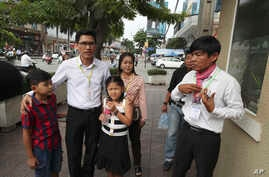 Journalists Uon Chhin, right, and Yeang Sothearin with his children enter the municipal court in Phnom Penh, Cambodia, Aug. 9, 2019. The two Cambodian journalists were on trial on espionage charges rights groups call a flagrant attack on press freedom.