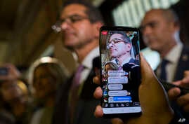 A person makes a live video as appointed Secretary of State Pedro Pierluisi arrives to the Senate, in San Juan, Puerto Rico, Thursday, August 1, 2019. Puerto Rican politics were in full-blown crisis as confirmation of Pierluisi, the nominee to…