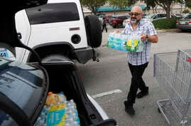Alvaro Figueroa loads his vehicle with bottled water at BJ's Wholesale Club in preparation for Hurricane Dorian, Thursday, Aug. 29, 2019, in Hialeah, Fla. Hurricane Dorian is heading towards Florida for a possible direct hit on the state over Labor…