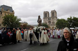 Catholic clergymen and pilgrims take part in an emotional procession with the statue of the Virgin Mary rescued from the April blaze past the fire-ravaged Notre Dame Cathedral to celebrate the Assumption of the Virgin in Paris, Thursday, Aug. 15,…