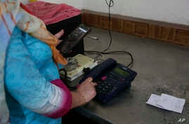 A Kashmiri woman makes a call to a relative after landline phones were restored in Srinagar, Indian controlled Kashmir, Thursday, Sept. 5, 2019. Indian authorities say they have restored all landline phones in the Himalayan region of Kashmir after…