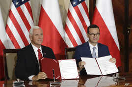 U.S. Vice President Mike Pence and Polish Prime Minister Mateusz Morawiecki display an agreement they signed in Warsaw, Poland, Sept. 2, 2019.