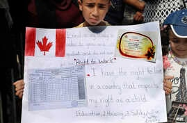 A Palestinian refugee boy holds a placard showing his school report card as hundreds of refugees request asylum at a rally outside the the Canadian Embassy, in Beirut, Lebanon, Thursday, Sept. 5, 2019.