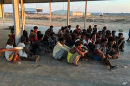 Rescued migrants sit on a coast some 100 kilometers (60 miles) east of Tripoli, Libya, Thursday, July 25, 2019. The U.N. refugee agency and the International Rescue Committee say up to 150 may have perished at sea off the coast of Libya. The country…