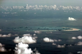 FILE - In this Monday, May 11, 2015, file photo, This aerial photo taken through a glass window of a military plane shows China's alleged on-going reclamation of Mischief Reef in the Spratly Islands in the South China Sea. The dispute over the…