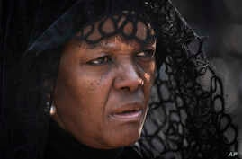 FILE- In this Thursday, Sept. 12, 2019, file photo, widow Grace Mugabe wears a black veil as she follows the casket of former president Robert Mugabe to an air force helicopter for transport to a stadium where it will lie in state, at his official…