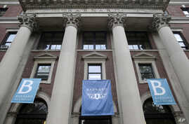 In this Thursday, May 28, 2015 photo, banners hang from a building at Barnard College in New York. Barnard, like other women's colleges, has always admitted only students born as women, but the class of 2020 may be different. Soon Barnard's trustees…