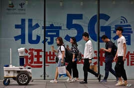 People walk toward a police robot mounted with surveillance cameras patrol past a 5G network advertisement at a shopping district in Beijing, Wednesday, May 15, 2019. U.S. officials listed $300 billion more of Chinese goods for possible tariff hikes…