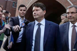 Devin Sloane, middle, leaves federal court after his sentencing in a nationwide college admissions bribery scandal, Tuesday, Sept. 24, 2019, in Boston. (AP Photo/Elise Amendola)