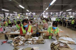 In this Oct. 24, 2017, photo, garment workers sew clothes at Pro Sports factory in Nam Dinh province, Vietnam.