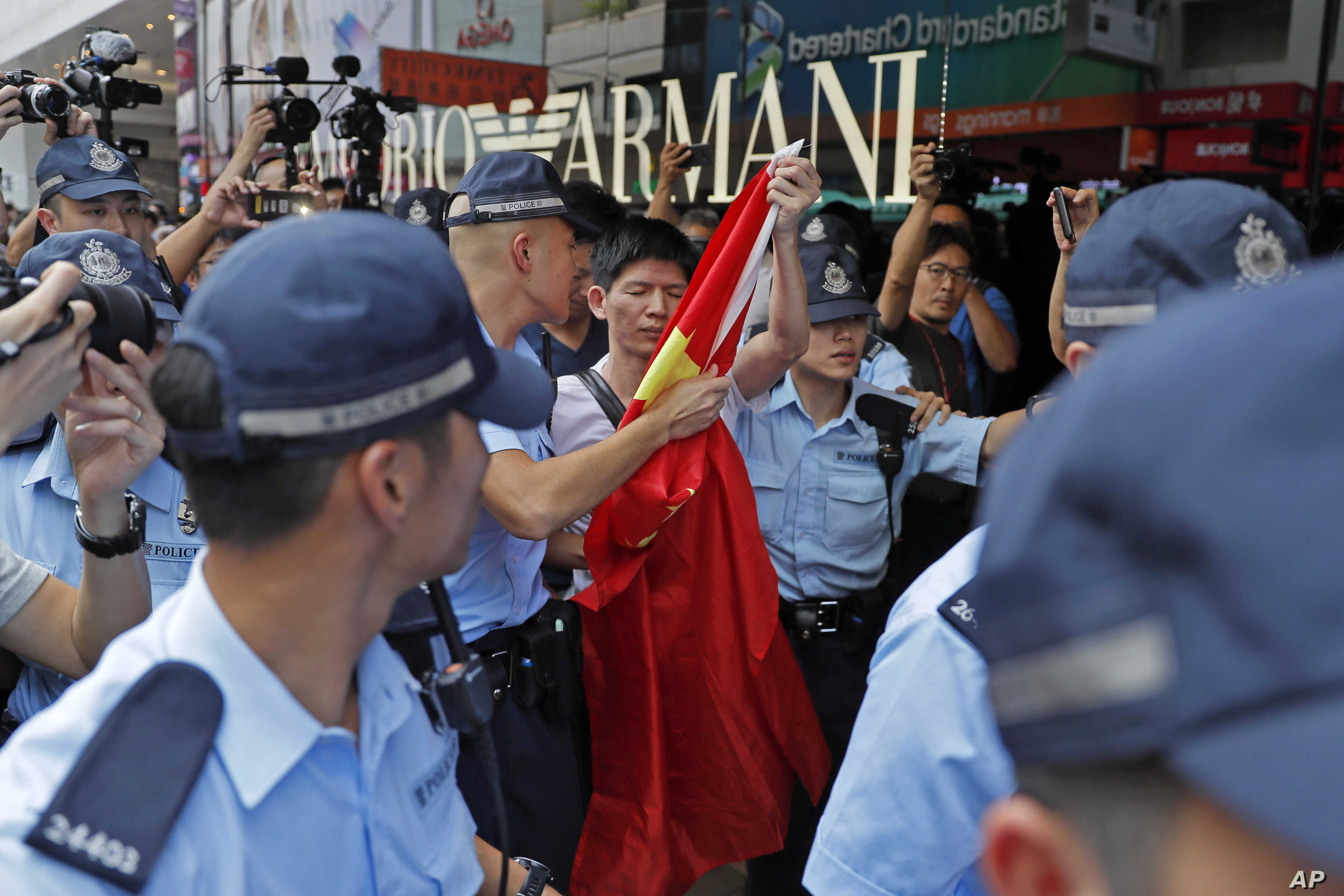 A pro-China supporter, holding a Chinese national flag at center, is escorted by police officers in a shopping mall in Hong Kong, Wednesday, Sept. 18, 2019. Activists involved in the pro-democracy protests in Hong Kong appealed to U.S. lawmakers…