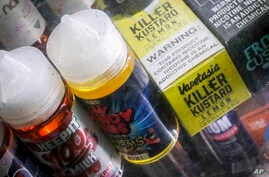 FILE - In this Sept. 16, 2019 file photo flavored vaping solutions are shown in a window display at a vape and smoke shop, in New York. Michigan has joined New York in banning the sale of flavored e-cigarettes as federal health officials investigate…