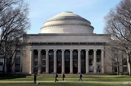"FILE - In this April 3, 2017 file photo, students walk past the ""Great Dome"" atop Building 10 on the Massachusetts Institute of Technology campus in Cambridge, Mass. Two prominent researchers are quitting MIT's Media Lab over revelations that the…"