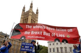 Anti-Brexit campaigner Steve Bray, centre, holds a banner near Parliament in London, Monday, Sept. 9, 2019. British Prime Minister Boris Johnson voiced optimism Monday that a new Brexit deal can be reached so Britain leaves the European Union by Oct…