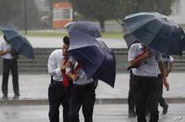 Pedestrians shield themselves from wind and rain brought by Typhoon Lingling Saturday, Sept. 7, 2019, in Pyongyang, North Korea. The typhoon passed along South Korea's coast has toppled trees, grounded planes and caused at least two deaths before…