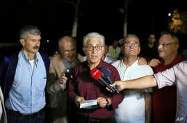 In this photo taken late Thursday, Sept. 12, 2019, Cartoonist Musa Kart, center, and four other journalists working with Turkey's leading opposition Cumhuriyet newspaper speak to the media in Istanbul. Turkey's state-run news agency says five jailed…