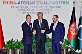 In this photo released by the Press Information Department, Pakistani Foreign Minister Shah Mahmood Qureshi, center, hand shakes jointly with Afghan counterpart Salahuddin Rabbani, right, and Chinese counterpart Wang Yi prior to a meeting in…