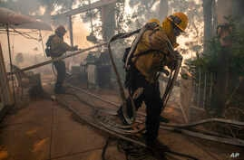 Firefighters pull hoses and spray flames behind a home in the Pacific Palisades area of Los Angeles, Monday, Oct. 21, 2019. (AP…