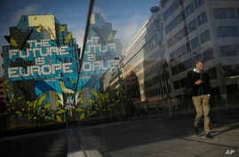 People walk past next to a pro-Europe street art painting in the European quarter in Brussels, Friday, Oct. 25, 2019. EU…