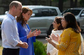 Britain's Prince William and his wife Kate speaks to teachers during their visit to a school in Islamabad, Pakistan, Tuesday,…