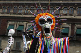 Performers in costume attend a Day of the Dead parade in Mexico City, Sunday, Oct. 27, 2019. The parade on Sunday marks the…