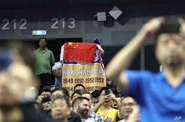 A fan drapes a Chinese national flag over an NBA banner during a preseason NBA basketball game between the Brooklyn Nets and…