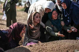 Relatives of Halil Yagmur, 64, who was killed Friday during mortar shelling from Syria, mourn over his grave at the cemetery in…