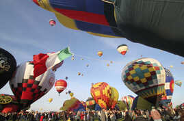 FILE - In this Oct. 2, 2011, file photo, thousands of spectators mingle among inflating hot air balloons at the 40th…