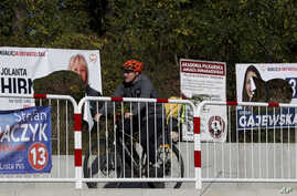 A cyclist rides past damaged electoral posters in Warsaw, Poland, Oct. 14, 2019.